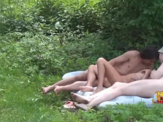 Slutty brunette in a group sex action on the nature